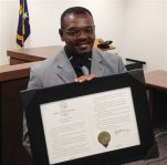 Henry McCollum holds a framed copy of his pardon before a hearing on compensation by the state for his wrongful conviction on Sept. 2, 2015 in Raleigh, N.C. McCollum was the state's longest serving death row inmate when he was released in 2014 after three decades in prison after being wrongfully convicted in a girl's death. (AP Photo/Jonathan Drew)