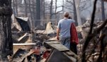 Richard and Kathie Reeves embrace as they stand in the remains of the home of close friends that was destroyed in a wildfire several days earlier, Tuesday, Sept. 15, 2015, in Middletown, Calif. The fire that sped through Middletown and other parts of rural Lake County, less than 100 miles north of San Francisco, has continued to burn since Saturday despite a massive firefighting effort. (AP Photo/Elaine Thompson)