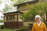 In this Monday, Oct. 5, 2015, photo, retired teacher Linda McQuillen stands in front of her home designed by the famous architect Frank Lloyd Wright in Madison, Wis. Wright experts on Tuesday were expected to reveal that the home built in 1917 near the University of Wisconsin campus, is an American System-Built House. That was part of Wright's effort to develop and market well-designed homes for any income level. It's the second time in four months that a Wright house has been rediscovered in Wisconsin. (AP Photo/Carrie Antlfinger)