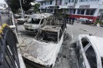 Thai policemen stand guard behind the burnt down vehicles at a police station in Phuket, Thailand, Sunday, Oct. 11, 2015. An angry crowd hurled homemade fire bombs and torched vehicles at a police station on Thailand's resort island of Phuket to protest the deaths of two young men who died in a motorcycle crash while being chased by police, authorities said Sunday. (AP Photo/Sumeth Panpetch)