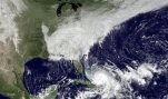 This satellite image taken Friday, Oct. 2, 2015 at 12:45 p.m. EDT, and released by the National Oceanic and Atmospheric Administration (NOAA), shows Hurricane Joaquin, bottom center, pounding the Bahamas and a deepening low pressure system on the U.S. east coast.  Millions along the east coast breathed a little easier Friday after forecasters said Hurricane Joaquin would probably veer out to sea instead of joining up with a drenching rainstorm that is bringing severe flooding to parts of the Atlantic Seaboard.  (NOAA via AP)