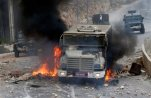 """An Israeli military vehicle drives through burning tires during a raid in the West Bank city of Nablus, Tuesday, Oct. 6, 2015. Israeli Prime Minister Benjamin Netanyahu warned Monday that he will use a """"strong hand"""" to quell violent Palestinian protests and deadly attacks, signaling that the current round of violence is bound to escalate at a time when a political solution to the conflict is increasingly distant. (AP Photo/Majdi Mohammed)"""
