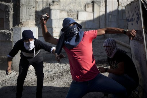 Palestinians throw stones during clashes with Israeli troops at Qalandia checkpoint between Jerusalem and the West Bank city of Ramallah, Tuesday, Oct. 6, 2015. A new generation of angry, disillusioned Palestinians is driving the current wave of clashes with Israeli forces: They are too young to remember the hardships of life during Israel's clampdown on the last major uprising, and after years of nationalist Israeli governments many have lost faith in statehood through negotiations and believe Israel only understands force. (AP Photo/Majdi Mohammed)