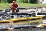 FILE - In this July 29, 2010, file photo, a worker monitors water in Talmadge Creek in Marshall Township, Mich., near the Kalamazoo River as oil from a ruptured pipeline, owned by Enbridge Inc., is trapped by booms.  The suit filed Thursday, Oct. 8, 2015 by the National Wildlife Federation says the federal Oil Pollution Act prohibits operators from handling, storing or transporting oil until their spill response plans get federal approval. The plans are supposed to make sure enough resources are available to contain and remove spilled oil and limit environmental damage. (AP Photo/Paul Sancya, File)