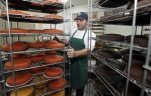 In this Wednesday, Oct. 28, 2015, John Farhoud works in his bakery in the Gratiot Central Market Building in Detroit. While Tommy Bedway, who owns the building, says his property value is up, others fear they could be priced out during the city's recovery as property values and rents rise. Farhoud says he's keeping his store, paying $2,000 rent on a month-to-month lease until something better comes along. (AP Photo/Carlos Osorio)