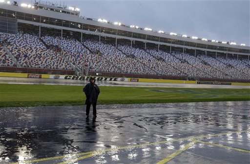 A security guard stands in the pouring rain on pit road before the scheduled start of the NASCAR Sprint Cup series auto race at Charlotte Motor Speedway in Concord, N.C., Saturday, Oct. 10, 2015. (AP Photo/Chuck Burton)