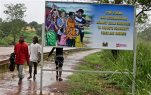 FILE - In this Aug. 12, 2015 photo, people walk past a billboard warning residents to stop the stigmatization of Ebola survivors, in Kenema, eastern Sierra Leone.  Johnson & Johnson has begun clinical trials for an Ebola vaccine in Sierra Leone. The vaccine regimen is part of a new study being conducted in Sierra Leone's Kambia district, where some of the country's most recent Ebola cases have been reported. The company said Friday, Oct. 9,  that the first volunteers have received the initial dose. (AP Photo/Sunday Alamba)
