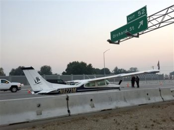 A small plane makes an emergency landing on I-84 in Boise, Idaho Tuesday, Oct. 13, 2015.  Two law enforcement agencies say the small craft touched down about 7 a.m. on the eastbound lanes and that there are no immediate reports of injuries or vehicles involved.  (AP Photo/Rebecca Boone)