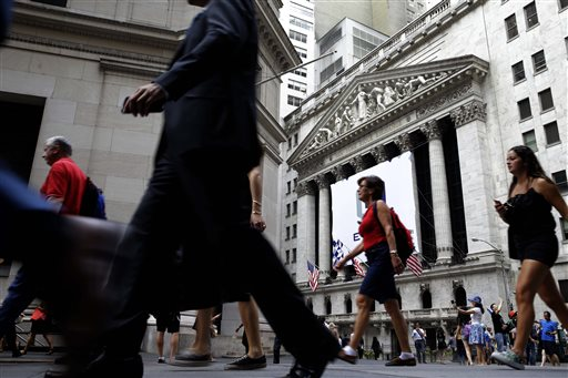 In this Monday, Aug. 24, 2015, photo, pedestrians walk past the New York Stock Exchange. Global stock markets were mixed Monday, Oct. 12, 2015, following Wall Street's gains as investors looked ahead to the week's Chinese trade data. (AP Photo/Seth Wenig)