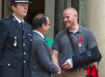 FILE - In this Aug. 24, 2015 file photo, French President Francois Hollande shakes hands with U.S. Airman Spencer Stone outside the Elysee Palace in Paris after Hollande awarded Stone and two friends with the French Legion of Honor for subduing a gunman on a Paris-bound train three days earlier. Stone is in stable condition Thursday, Oct. 8, 2015, after being stabbed in Sacramento, Calif., according to an Air Force spokesman. (AP Photo/Kamil Zihnioglu, File)