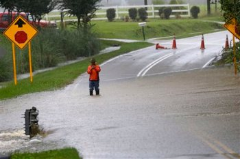 A man stands in floodwaters covering a road in Florence, S.C., Sunday, Oct. 4, 2015, as heavy rains continue to cause flooding in many parts of the state. The rainstorm drenching the U.S. East Coast brought more misery Sunday to South Carolina, cutting power to thousands, forcing hundreds of water rescues and closing many roads because of floodwaters. (AP Photo/Gerry Broome)