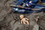 A doll and clothing lay in the mud as rescue workers continue to search the site of a mudslide in Cambray, a neighborhood in the suburb of Santa Catarina Pinula, on the outskirts of Guatemala City, Saturday, Oct. 3, 2015. Rescue workers recovered more bodies Saturday after a hillside collapsed on homes late Thursday, while more are feared still buried in the rubble. (AP Photo/Luis Soto)