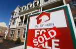 FILE - In this Jan. 8, 2015, file photo, a sign with a sold sticker is posted in front of a row of new town homes in Richmond, Va. The Commerce Department reports on sales of new homes in October, on Wednesday, Nov. 25, 2015. (AP Photo/Steve Helber, File)