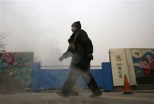 A woman wearing a mask to protect herself from pollutants walks past a construction site on a heavily polluted day in Beijing, Monday, Nov. 30, 2015. Beijing on Sunday, Nov. 29 issued its highest smog alert of the year following air pollution in capital city reached hazardous levels as smog engulfed large parts of the country despite efforts to clean up the foul air. (AP Photo/Andy Wong)