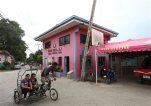 In this photo taken Sept 25, 2015, a man pedals past a village hall in Eileen Ontong's neighborhood Thursday, Sept. 24, 2015 in Ibabao village, Cordova township, Cebu province in central Philippines. Ontong, along with her husband Wilfredo, was arrested May 28, 2013, by agents of the National Bureau of Investigation in a raid at their house allegedly after engaging in a cybersex syndicate. Marine Chief Warrant Officer 4 Daniel E. DeSmit was the biggest single customer of Ontong's operation, according to a U.S. official familiar with the case. (AP Photo/Chester Baldicantos)