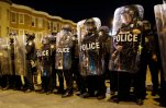 FILE - In this April 28, 2015 file photo, police stand in formation as a curfew approache in Baltimore, a day after unrest that occurred following Freddie Gray's funeral. On the campaign trail, among candidates of both parties, the idea of locking up drug criminals for life is a lot less popular than it was a generation ago. The 2016 presidential race has accelerated an evolution away from the traditional tough-on-crime candidate. A Republican Party that's long taken a law-and-order stance finds itself desperate to improve its standing among minority voters while Democratic candidates are also being drawn into national conversations on policing, drug crimes and prison costs. (AP Photo/Patrick Semansky, File)