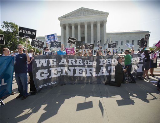 "FILE - In this June 30, 2014 file photo, demonstrators stand on the steps outside the Supreme Court in Washington, where the court was poised to deliver its verdict in a case that weighs the religious rights of employers and the right of women to the birth control of their choice. The Supreme Court is wading into its fourth dispute over President Barack Obama's 5-year-old health care overhaul. The newest ""Obamacare"" case involves objections by faith-based hospitals, colleges and charities to the process the administration devised to spare them from paying for contraceptives for women covered under their health plans, and yet ensure that those women can obtain birth control at no extra cost. (AP Photo/Pablo Martinez Monsivais, File)"