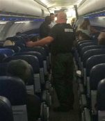 This Tuesday, Nov. 3, 2015, photo provided by Bill McCarthy shows airport police aboard a plane after an emergency landing at Eisenhower National Airport in Wichita, Kan. The U.S. Attorney's Office says a disruptive passenger who forced the diversion of the American Airlines flight from Phoenix to New York will face federal charges. (Bill McCarthy via AP)