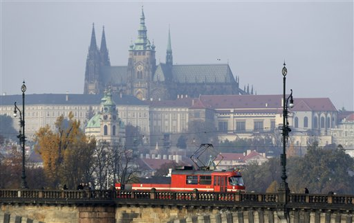 In this picture taken on Wednesday, Nov. 4, 2015, a special tram used for lubricating tracks crosses a bridge in Prague, Czech Republic. The unusual, convertible looking like vehicle with the open back part appeared on the tracks of Prague in January and has attracted unexpected attention and gained thousands of fans. The Prague castle is in the background. (AP Photo/Petr David Josek)