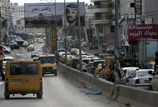 In this Tuesday, Nov. 10, 2015 photo, Palestinians drive near the Qalandia checkpoint between Jerusalem and the West Bank city of Ramallah. A pair of new mobile apps hopes to help Palestinians navigate their way around snarled traffic at Israeli checkpoints in the West Bank, offering a high-tech response to an intractable problem: constant, burdensome and often seemingly random restrictions on movement. (AP Photo/Majdi Mohammed)