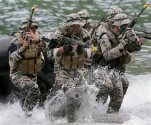 """Philippine Marines from the Naval Special Operations Group (NAVSOG) storm the beach to simulate an """"extraction"""" of a kidnapped victim as they kick off a five-day amphibious military exercise at the Philippine Marines training center in Ternate, Cavite province, about 50 miles (80kms) south of Manila, Philippines Thursday, Sept. 24, 2015. The naval exercise dubbed PAGSISIKAP 2015 is aimed at enhancing capability of their fleet and forces as well as to strengthen interoperability of the Marines. (AP Photo/Bullit Marquez)"""