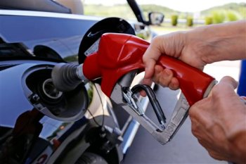 FILE - In this Thursday, July 16, 2015, file photo, a customer re-fuels her car at a Costco in Robinson Township, Pa. The plunging price of oil in 2016 is dragging stock markets to their worst start to a year ever, even though low fuel prices are great for consumers and most companies. (AP Photo/Gene J. Puskar, File)