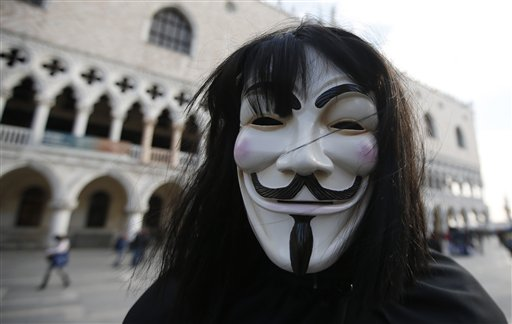 A man wearing an Anonymous mask is seen prior to the Carnival Grand Opening show, in Venice, Italy, Saturday, Jan. 23, 2015. The Venice carnival in the historical lagoon city attracts people from around the world. (AP Photo/Luca Bruno)