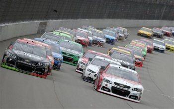 Kasey Kahne, left, and Kevin Harvick lead the field through the first turn during the NASCAR Sprint Cup series auto race at Michigan International Speedway, Sunday, June 14, 2015, in Brooklyn, Mich. (AP Photo/Bob Brodbeck)