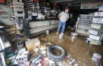 Paul Raines looks over his flooded Western Auto store in Rainelle, W. Va., Saturday, June 25, 2016. Heavy rains that pummeled West Virginia left multiple people dead, and authorities said Saturday that an unknown number of people in the hardest-hit county remained unaccounted for. (AP Photo/Steve Helber)
