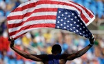 United States athlete Will Claye celebrates with an American flag after winning the silver medal in the men's triple jump in the 2016 Summer Olympics in Rio de Janeiro. The unity and pride most Americans show for Team USA during the Olympic games contrast sharply with most attitudes toward the 2016 presidential election and the state of the nation. (Charlie Riedel/AP)