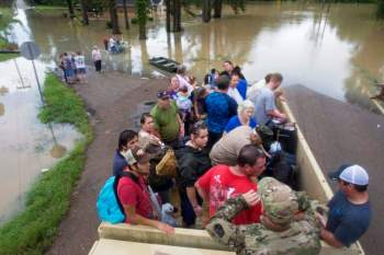 Sgt. Brad Stone of the Louisiana Army National Guard gives safety instructions to people loaded on a truck after they were stranded by rising floodwater near Walker, Louisiana, after heavy rains inundated the region, Sunday, Aug. 14, 2016. (Max Becherer/AP)