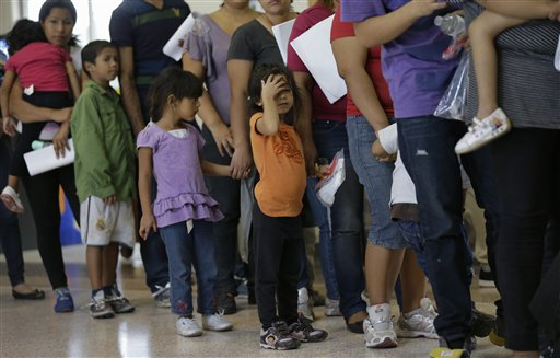 FILE - In this June 20, 2014, file photo, immigrants who entered the U.S. illegally stand in line for tickets at the bus station after they were released from a U.S. Customs and Border Protection processing facility in McAllen, Texas. (AP Photo/Eric Gay, File)