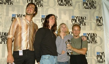"In this file photo, members of Nirvana, from left, Krist Novoselic, Dave Grohl and Kurt Cobain, appear at the MTV Video Music Awards on Sept. 2, 1993. The unidentified man at right was not a member of the band. Nirvana's iconic rock album ""Nevermind"" turns 25 on Saturday. (AP file)"