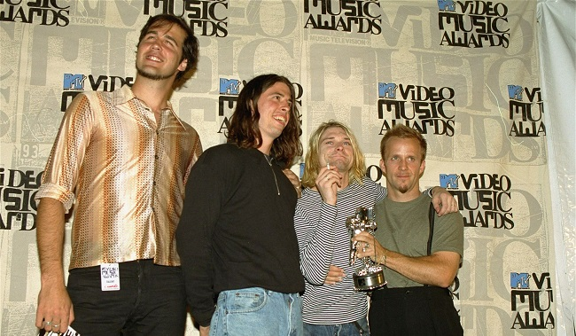 """In this file photo, members of Nirvana, from left, Krist Novoselic, Dave Grohl and Kurt Cobain, appear at the MTV Video Music Awards on Sept. 2, 1993. The unidentified man at right was not a member of the band. Nirvana's iconic rock album """"Nevermind"""" turns 25 on Saturday. (AP file)"""
