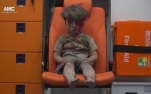 FILE - In this frame grab taken from video provided by the Syrian anti-government activist group Aleppo Media Center (AMC), 5-year-old Omran Daqneesh sits in an ambulance after being pulled out or a building hit by an airstirke, in Aleppo, Syria, Wednesday, Aug. 17, 2016. The White Helmets, were among the crowd of first responders who pulled Daqneesh and his family from the rubble of their apartment building Wednesday night. (Aleppo Media Center via AP)
