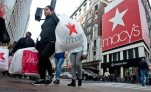 FILE - In this Nov. 27, 2015 file photo, shoppers carry bags as they cross a pedestrian walkway near Macy's in Herald Square in New York.  (AP Photo/Bebeto Matthews)