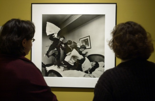 "Patrons view a photo of the Beatles, engaged in a pillow fight, that is part of an exhibit entitled, ""The Beatles: Now and Then,"" a collection of photographs by photojournalist Harry Benson at the Albany Institute of History and Art in Albany, N.Y., Friday, Jan. 3, 2003. Through his photos, Benson captured personal and intimate details of the Beatles during their first American tour, offering insight into the world of the young rock icons and those around them. (AP Photo/Tim Roske)"