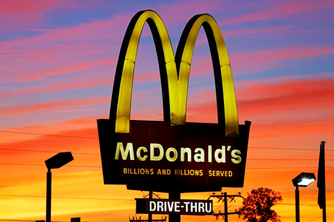 FILE - In this Saturday, Oct. 10, 2015, file photo, the sun sets behind a McDonald's in Ebensburg, Pa. (AP Photo/Gene J. Puskar, File)