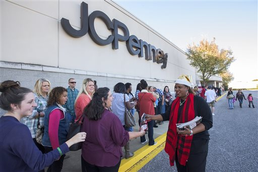 FILE - In this Thursday, Nov. 26, 2015, file photo, J.C. Penney General Manager Bridie Clinkscales hands out sales papers to Thanksgiving Day shoppers as they line up outside of the store at Eastdale Mall in Montgomery, Ala. (Mickey Welsh/The Montgomery Advertiser via AP, File)