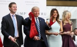 Republican presidential candidate Donald Trump, together with his family, from left, Eric Trump, Melania Trump and Tiffany Trump, waves part of a ribbon after cutting the ribbon during the grand opening of Trump International Hotel in Washington, Wednesday, Oct. 26, 2016. (Manuel Balce Ceneta/AP)