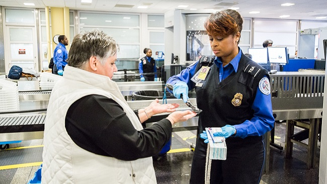 Transportation Security Officer Cacoya Hal performs a security screening on Anita Collins at Ronald Reagan Washington National Airport (Courtesy: TSA/DHS).