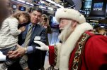Piper Foley, 4, daughter of New York Stock Exchange Senior Vice President Douglas Foley, meets Santa Claus from the Macy's Thanksgiving Parade, on the floor of the New York Stock Exchange before the opening bell Wednesday, Nov. 25, 2015. (AP Photo/Richard Drew)