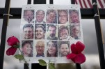 In this Nov. 18, 2016 photo, a faded photo collage showing images of the 14 victims who were killed in the Dec. 2, 2015, San Bernardino terror attack is adorned with artificial flowers at a makeshift memorial near the Inland Regional Center in San Bernardino, Calif., where the shooting took place. (AP Photo/Jae C. Hong)