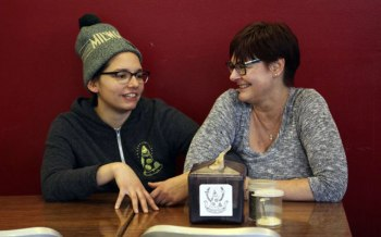 In this Jan. 9, 2017, photo, Andrea Ledesma, left, talks with her mother, Cheryl Romanowski, at Classic Slice pizza restaurant, where Ledesma works, in Milwaukee. Ledesma, 28, says her parents owned a house and were raising kids by her age. Not so for her, even though she has a college degree. (AP Photo/Carrie Antlfinger)
