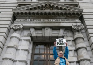 Karen Shore holds up a sign outside of the 9th U.S. Circuit Court of Appeals in San Francisco, Tuesday, Feb. 7, 2017. A panel of appeals court judges reviewing President Donald Trump's travel ban hammered away Tuesday at the federal government's arguments that the states cannot challenge the order. (AP Photo/Jeff Chiu)