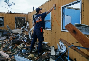 New Orleans Firefighter Jared Carter spray paints a search signal after conducting a secondary search of homes damaged by a tornado that touched down yesterday in eastern New Orleans, Wednesday, Feb. 8, 2017.  Officials say tornadoes that struck in southeastern Louisiana destroyed homes and businesses, flipped vehicles and left thousands without power.  (AP Photo/Max Becherer)