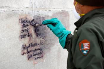 A U.S. Park Service employee works to clean graffiti off of the Washington Monument, Tuesday, Feb. 21, 2017, in Washington. U.S. Park Police spokeswoman Sgt. Anna Rose said that the messages written in permanent marker were discovered over the holiday weekend at the Lincoln Memorial, the Washington Monument and the World War II Memorial. (AP Photo/Alex Brandon)
