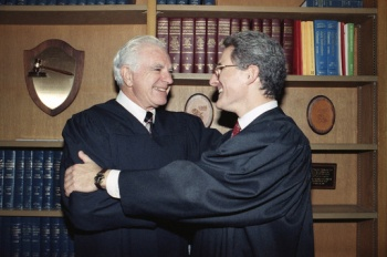 """FILE - In this Friday, Oct. 13, 1989, file photo, retired Judge Joseph A. Wapner of TV's 'The People's Court' congratulates his son, Judge Frederick N. Wapner, right, as he was enrobed as a Municipal Court judge in Los Angeles. Wapner, who presided over """"The People's Court"""" with steady force during the heyday of the reality courtroom show, has died. Wapner died at home in his sleep Sunday, Feb. 26, 2017, according to his son, David Wapner. (AP Photo/Nick Ut, File)"""